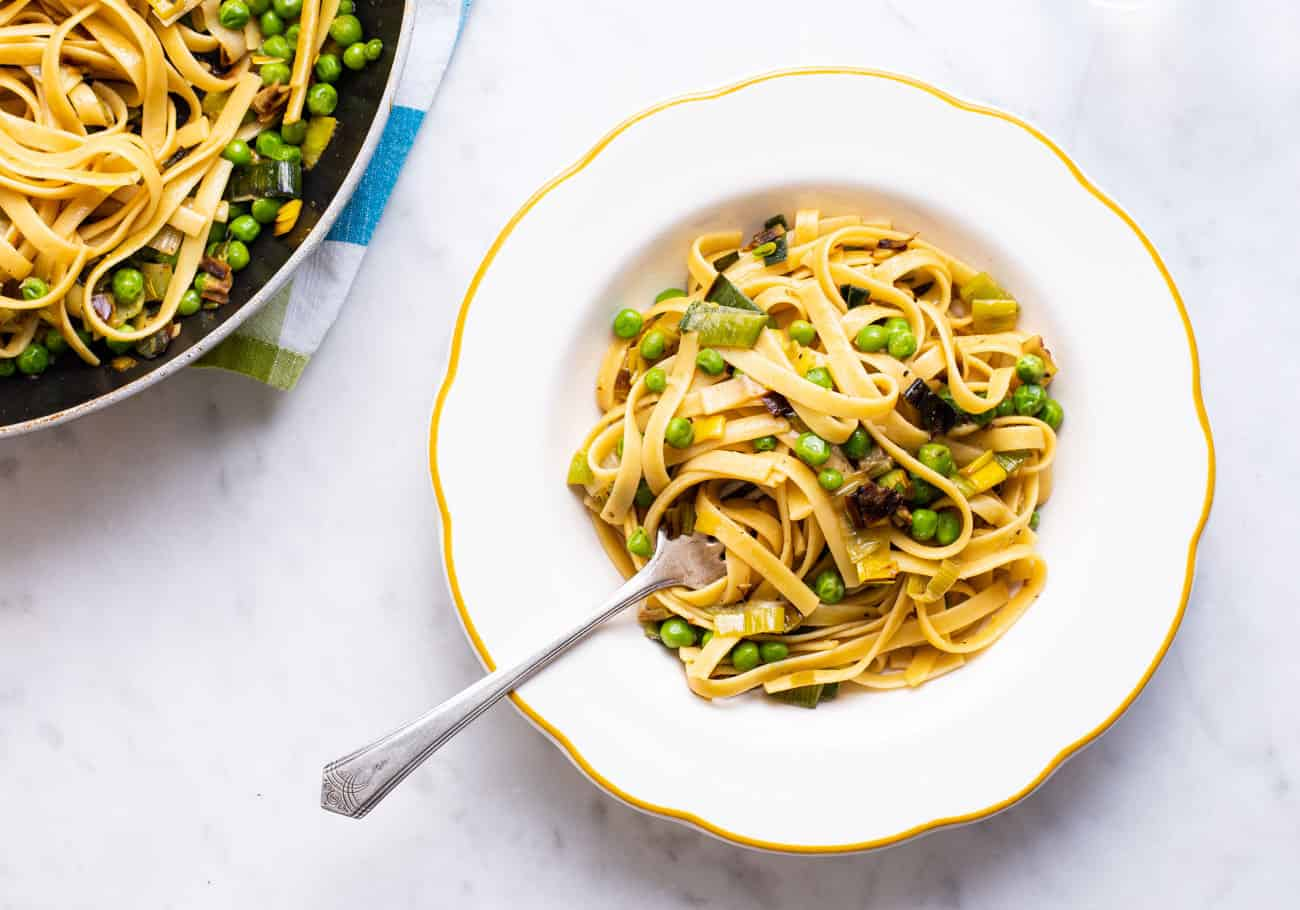 Vegan pasta with leeks and peas in a vintage scalloped bowl