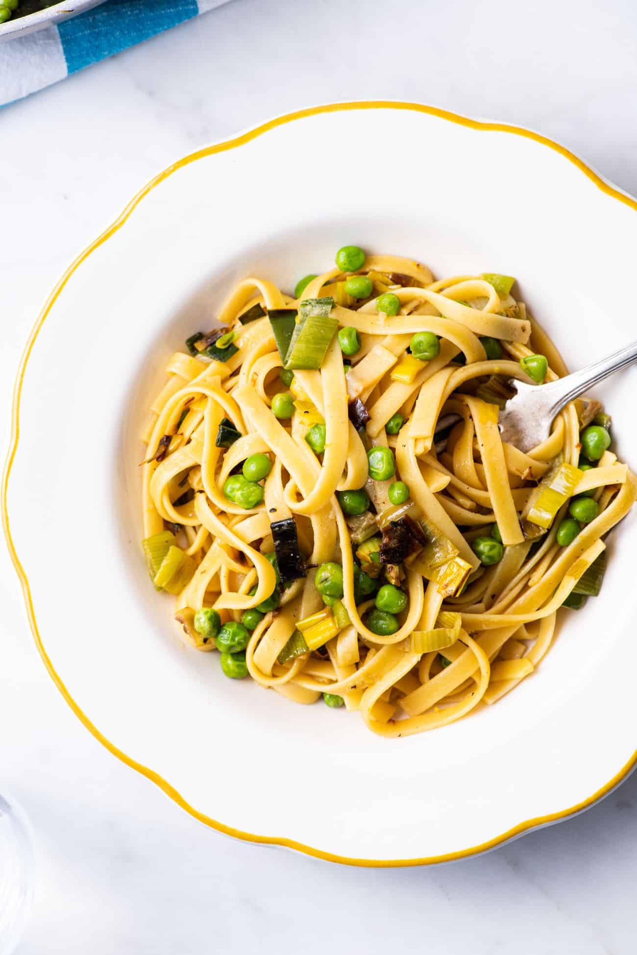 Vegan leek pasta with peas in a vintage scalloped bowl