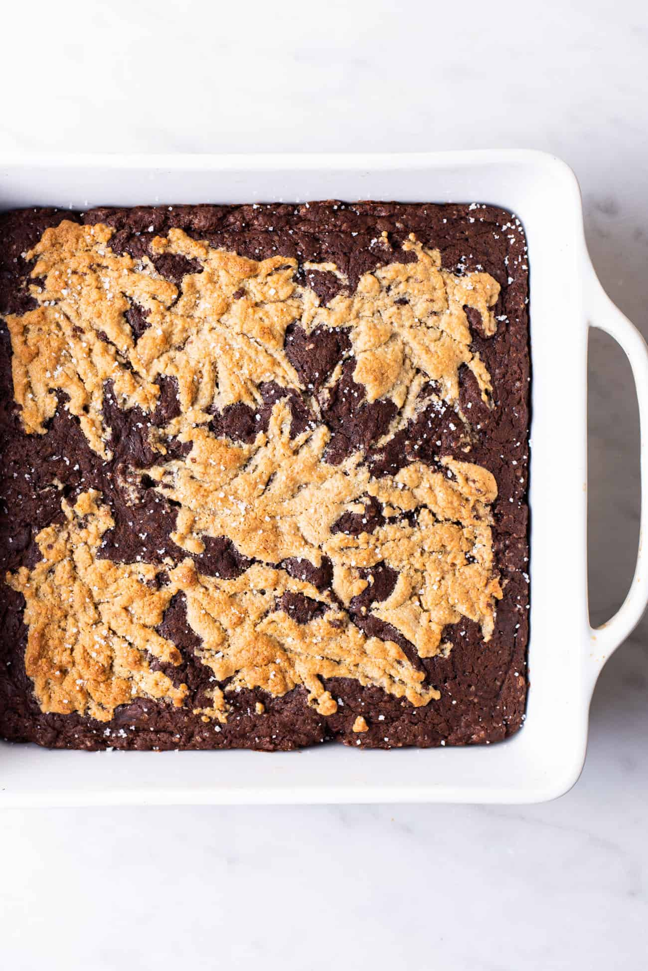 """Freshly baked brownies in a 8x8"""" ceramic pan with a golden brown tahini-miso swirl"""