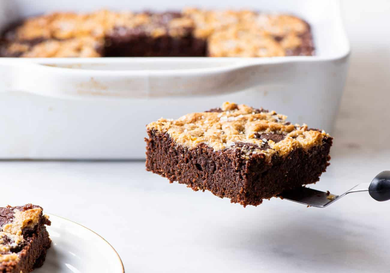 A tahini brownie being pulled out of a baking pan with a small offset spatula