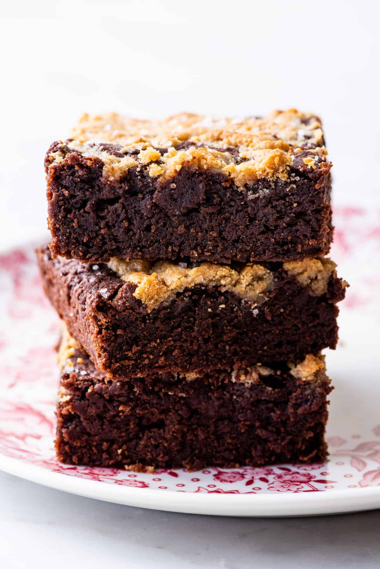A stack of tahini-miso brownies on a pink vintage plate