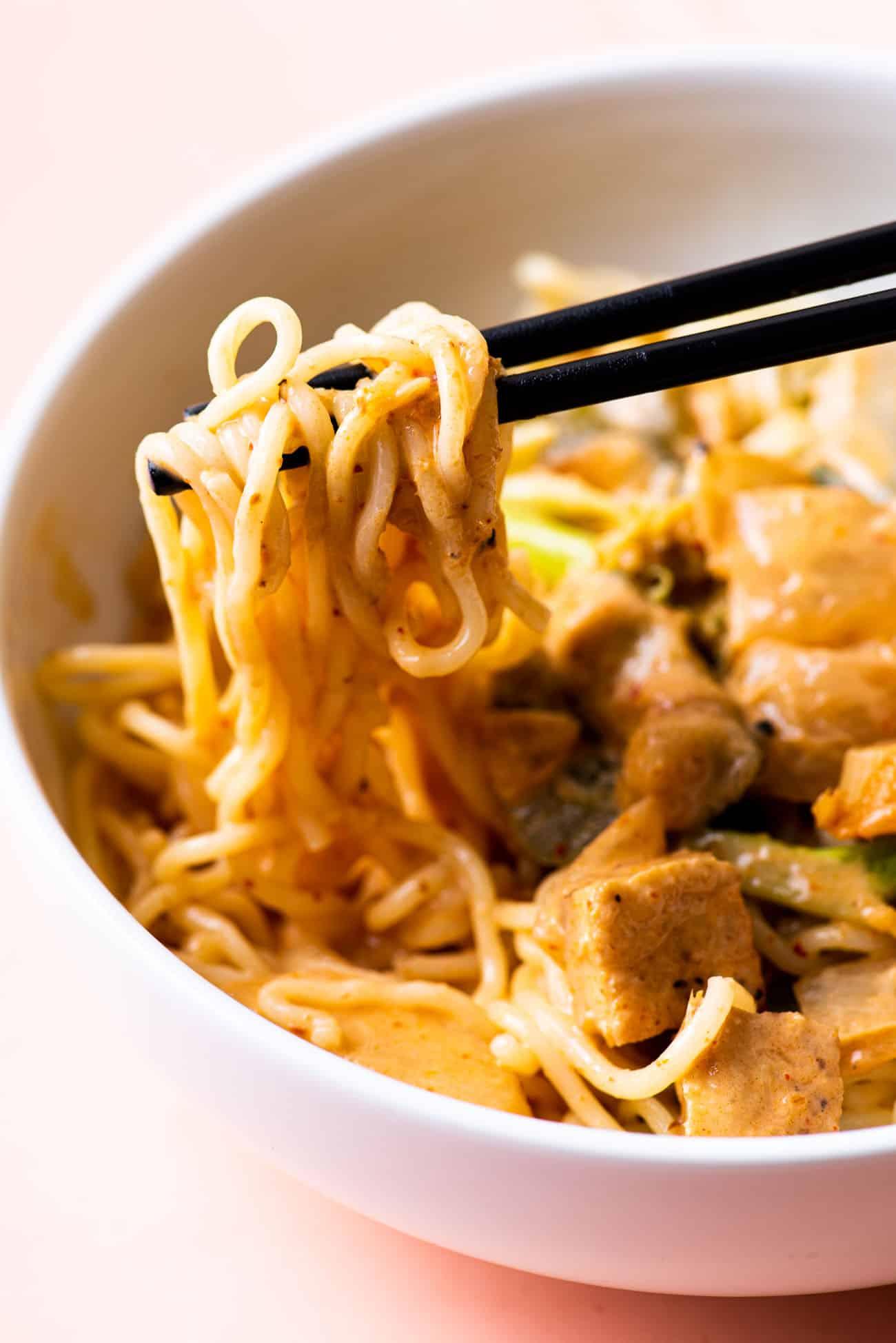 Close-up of black chopsticks holding creamy curry noodles
