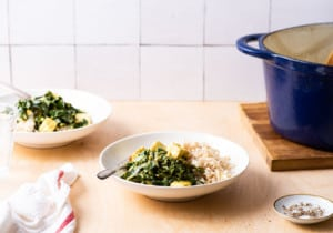Vegan saag paneer in white bowls with brown basmati rice on a wooden counter with a tiled backsplash