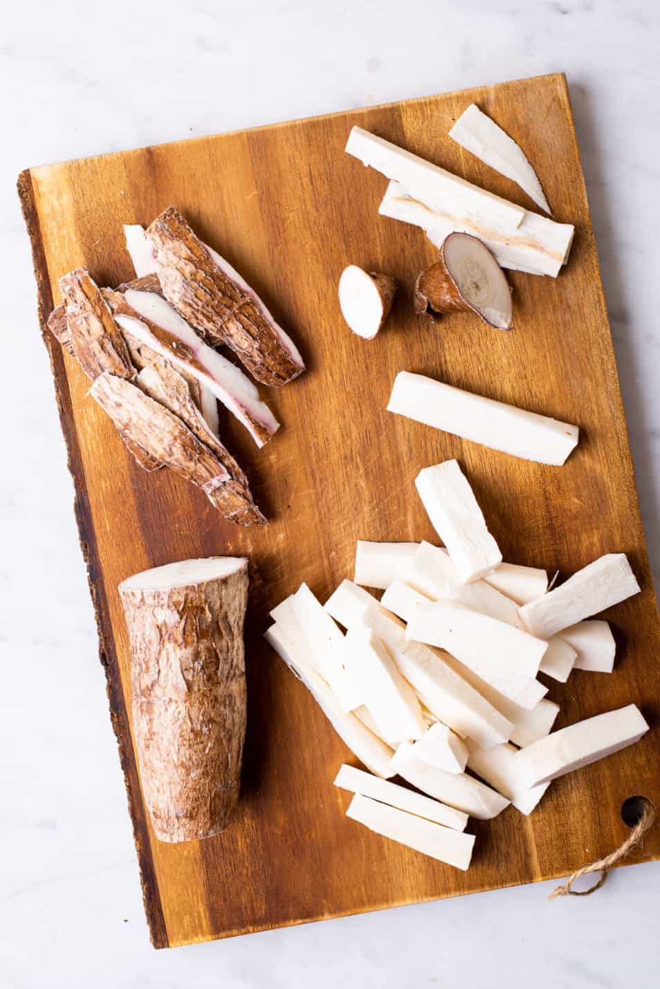 Peeled and chopped yuca on a cutting board.