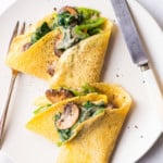Savory chickpea crepes folded into triangle and filled with a creamy vegan spinach and mushroom filling.