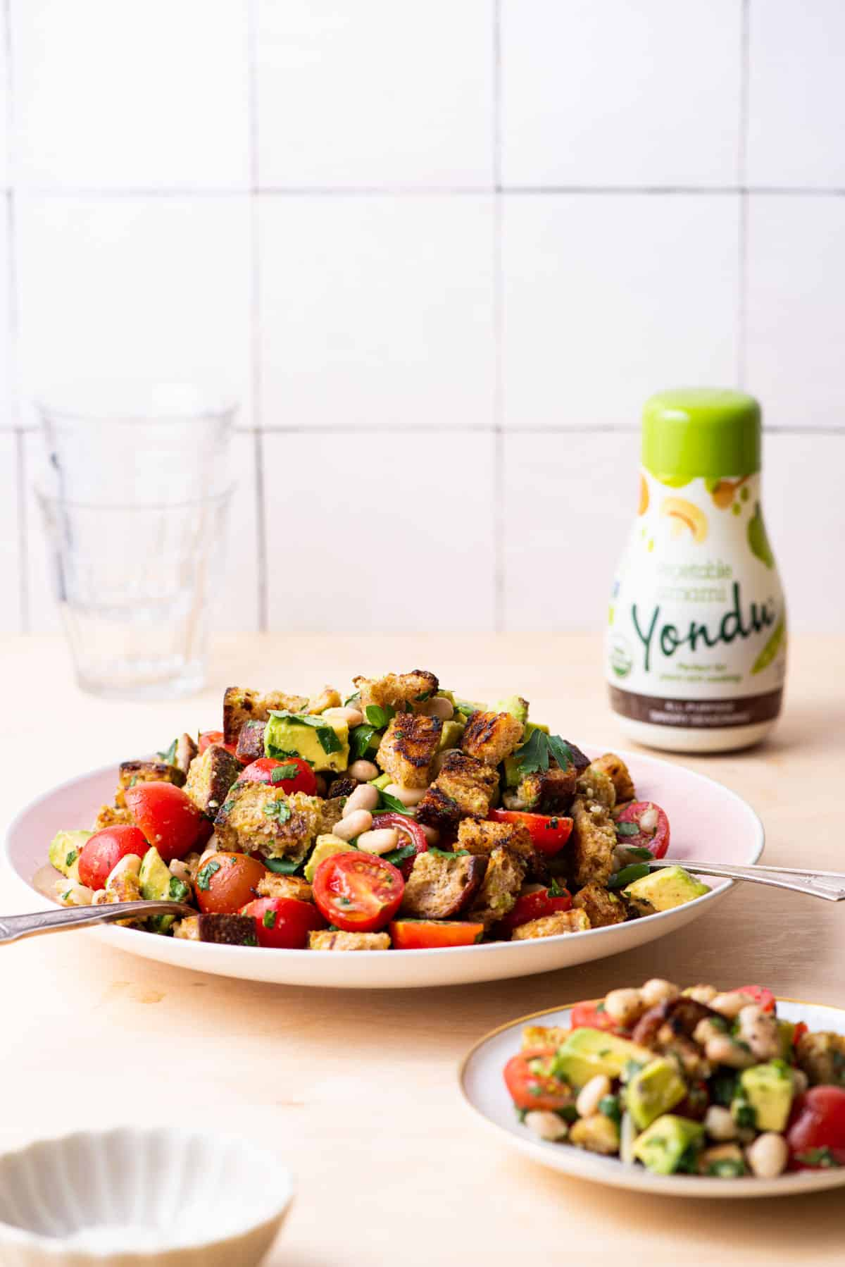 Panzanella salad on a wooden counter next to stacked glasses and a bottle of Yondu.