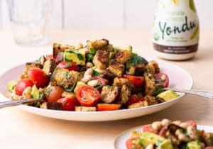 Panzanella with beans, tomatoes, and avocado on a pink platter.