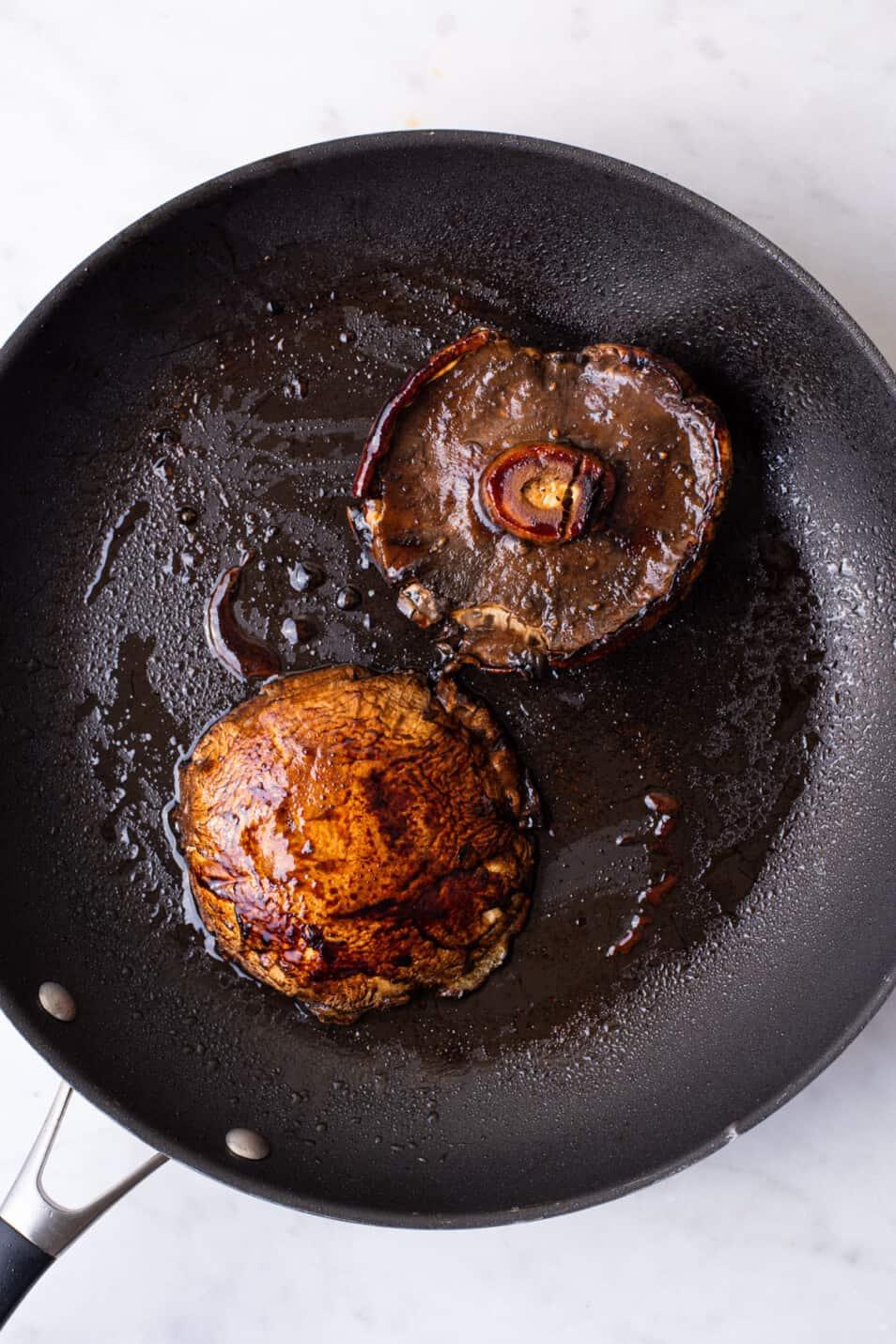 Balsamic portobello mushrooms, seared in a skillet.