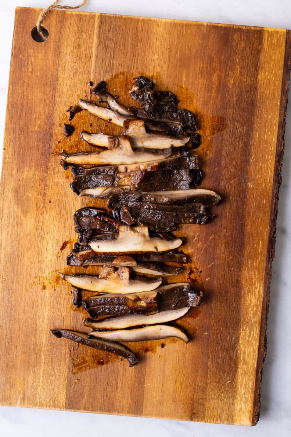 Sliced balsamic portobello mushrooms on a wooden board.