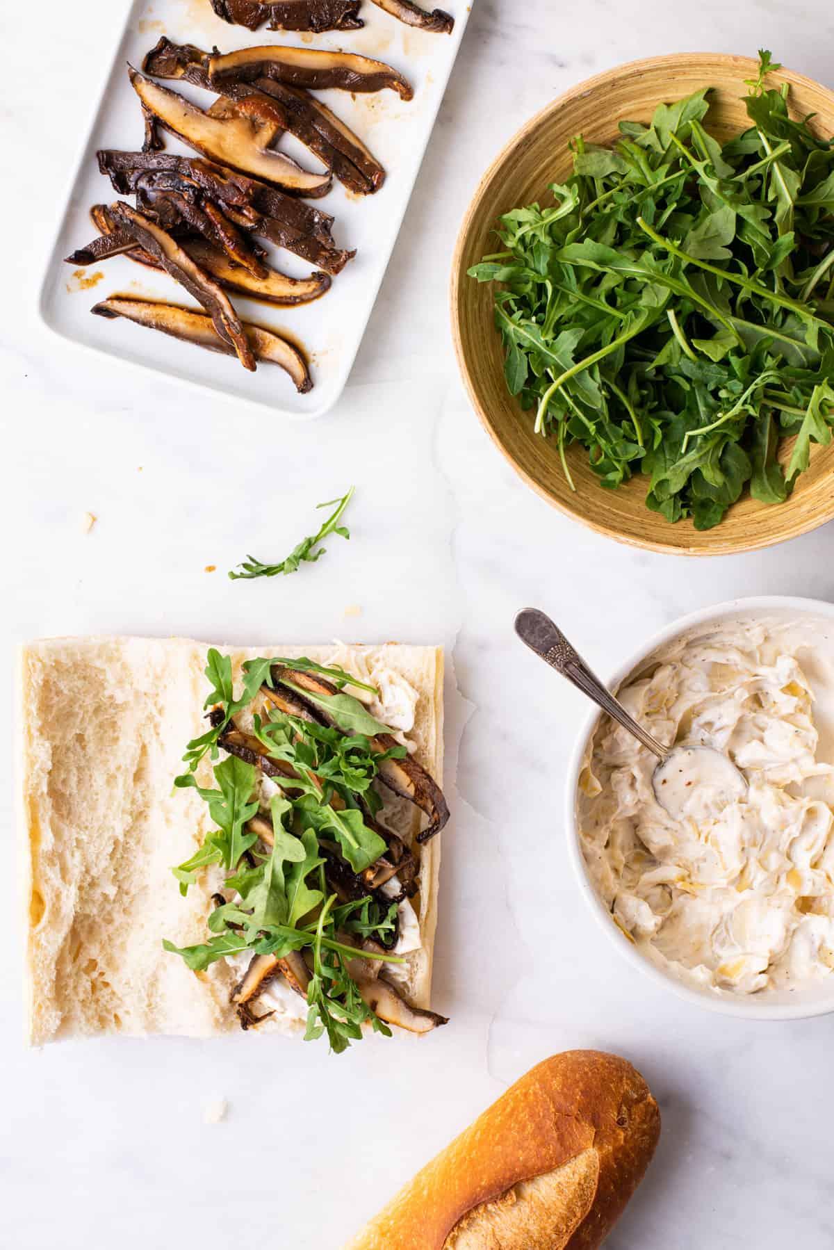 Assembling portobello sandwiches with arugula and artichoke mayo.