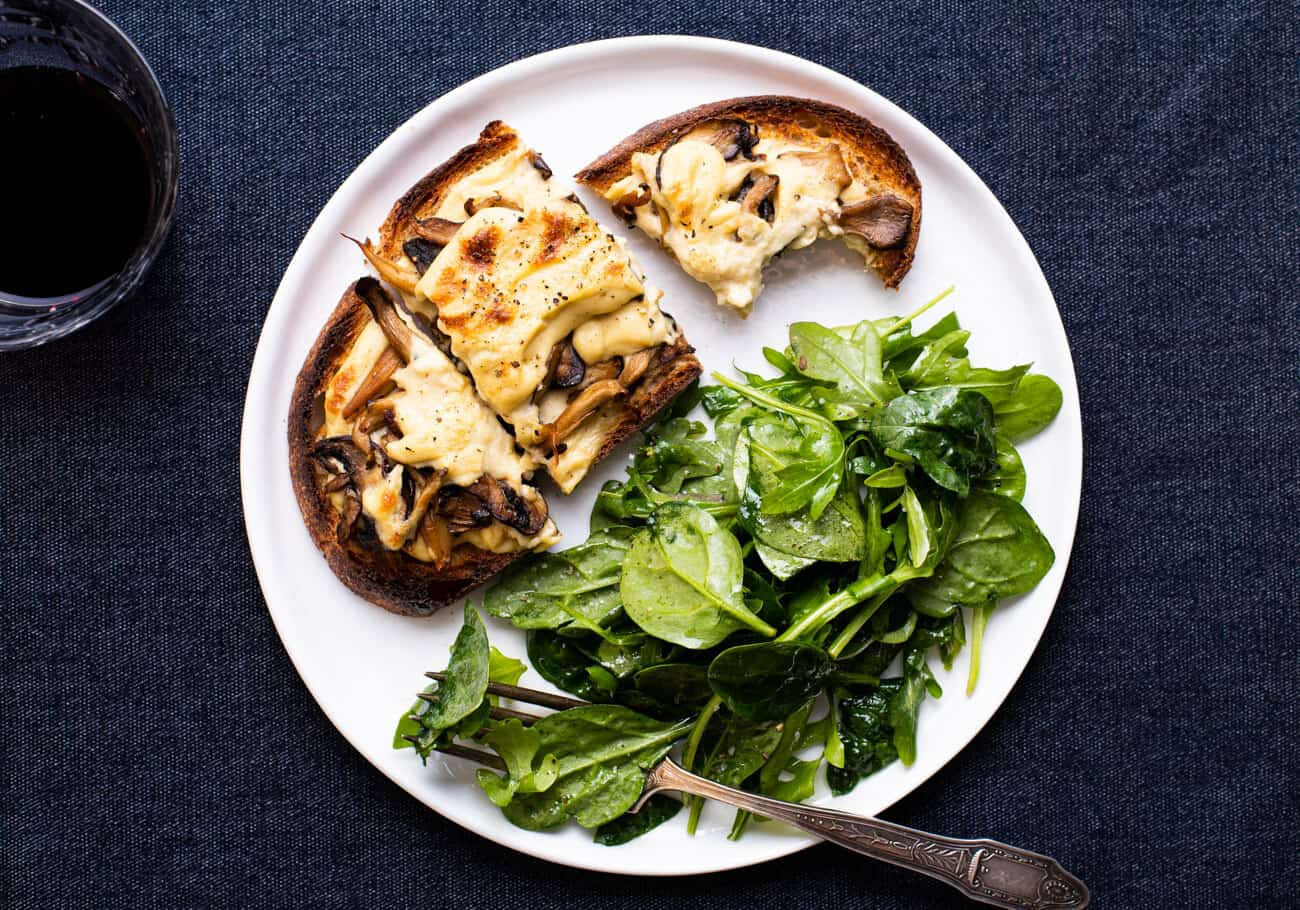 Creamy vegan mushroom tartine on a white plate with green salad.