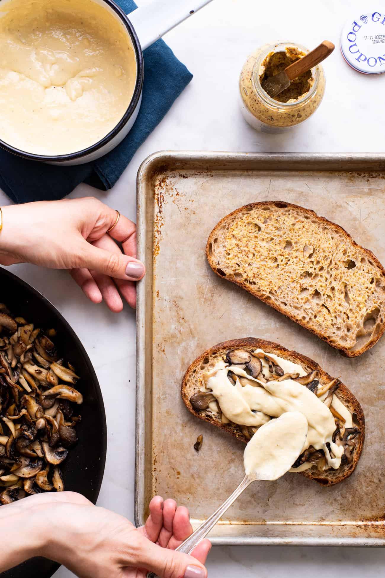 Woman's hands assembling vegan mushroom toasts.