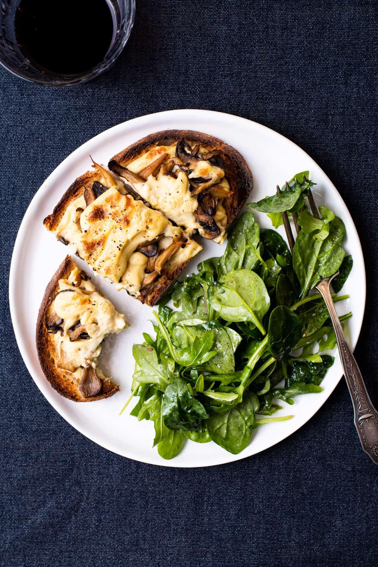 Creamy vegan mushroom tartine on a white plate with green salad.