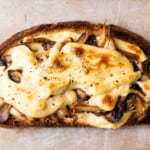"""Broiled open-faced vegan mushroom toast with melty """"cheese"""" sauce."""