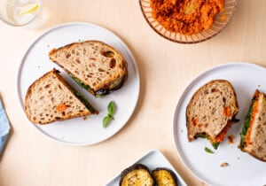 Roasted eggplant sandwiches with romesco sauce on white plates on a wooden table.