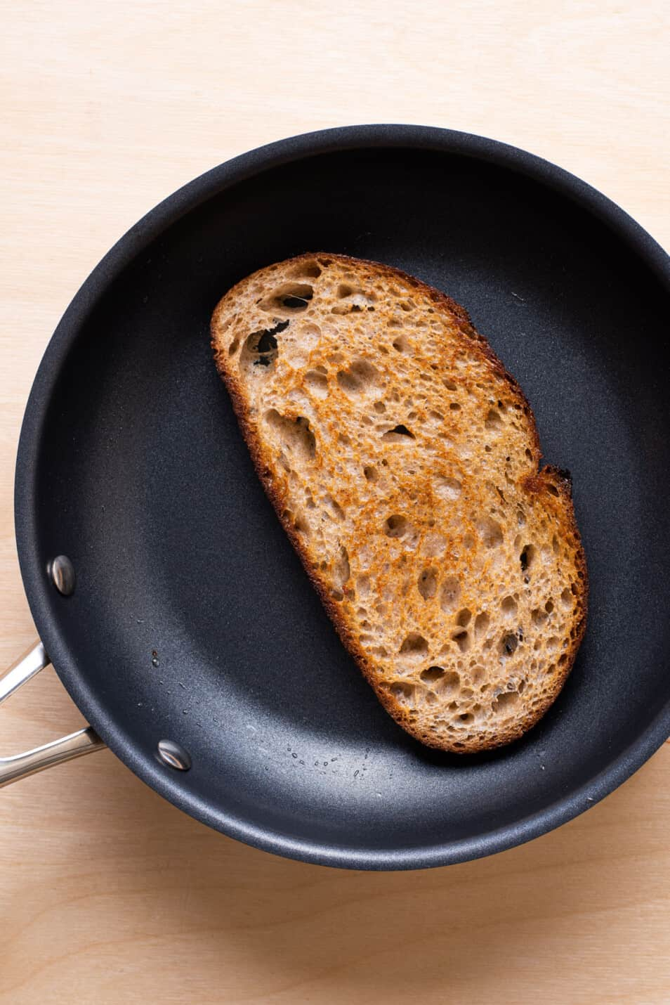A slice of bread toasted in olive oil in a skillet.