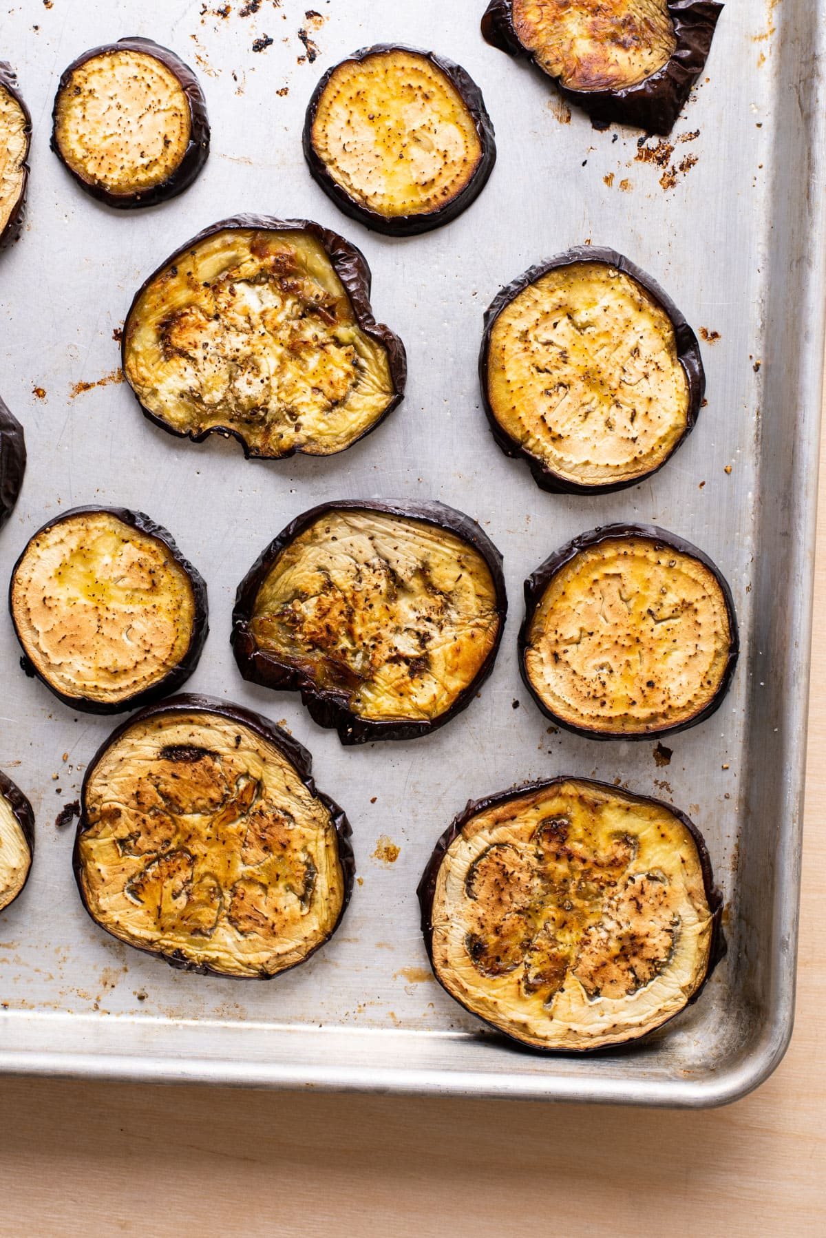 Roasted eggplant rounds on a baking sheet.