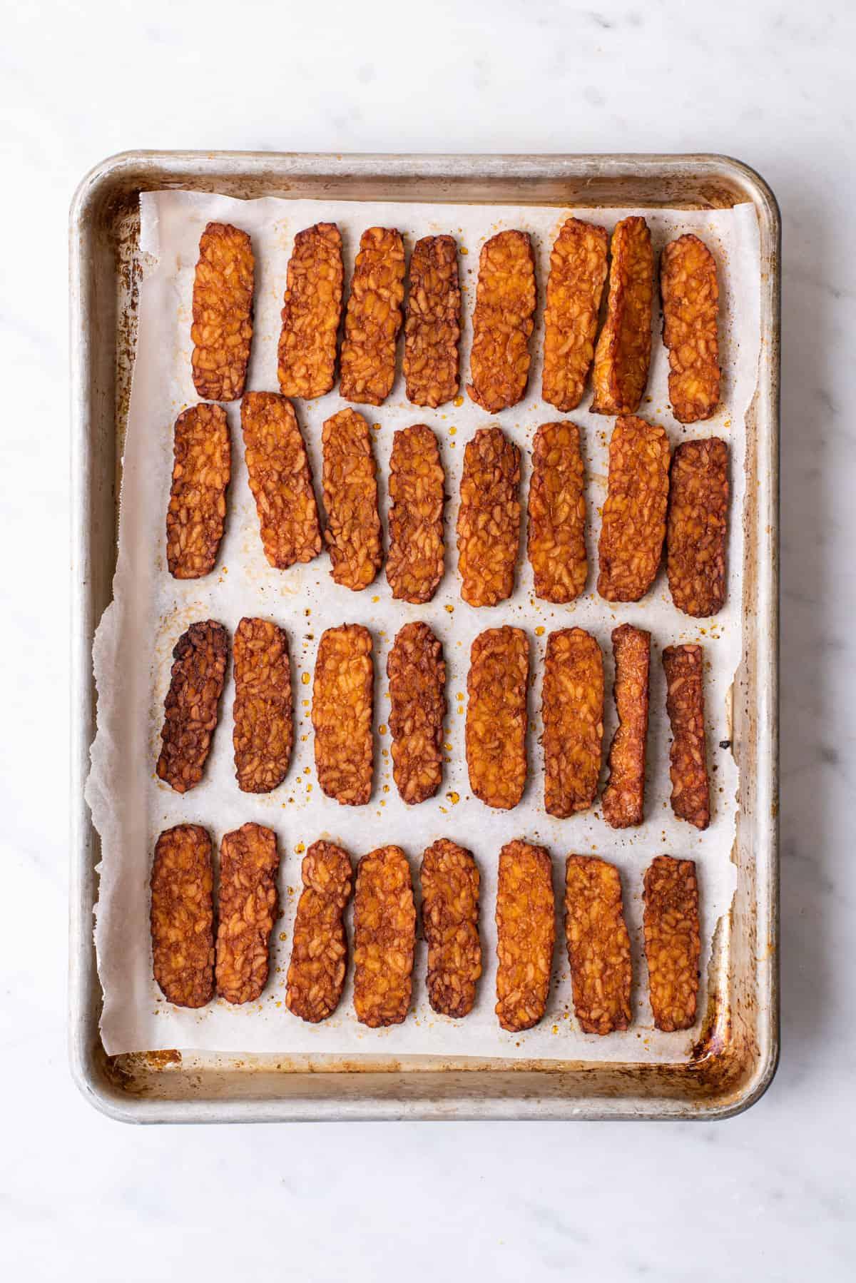 Baked tempeh bacon strips on a quarter-sheet pan.