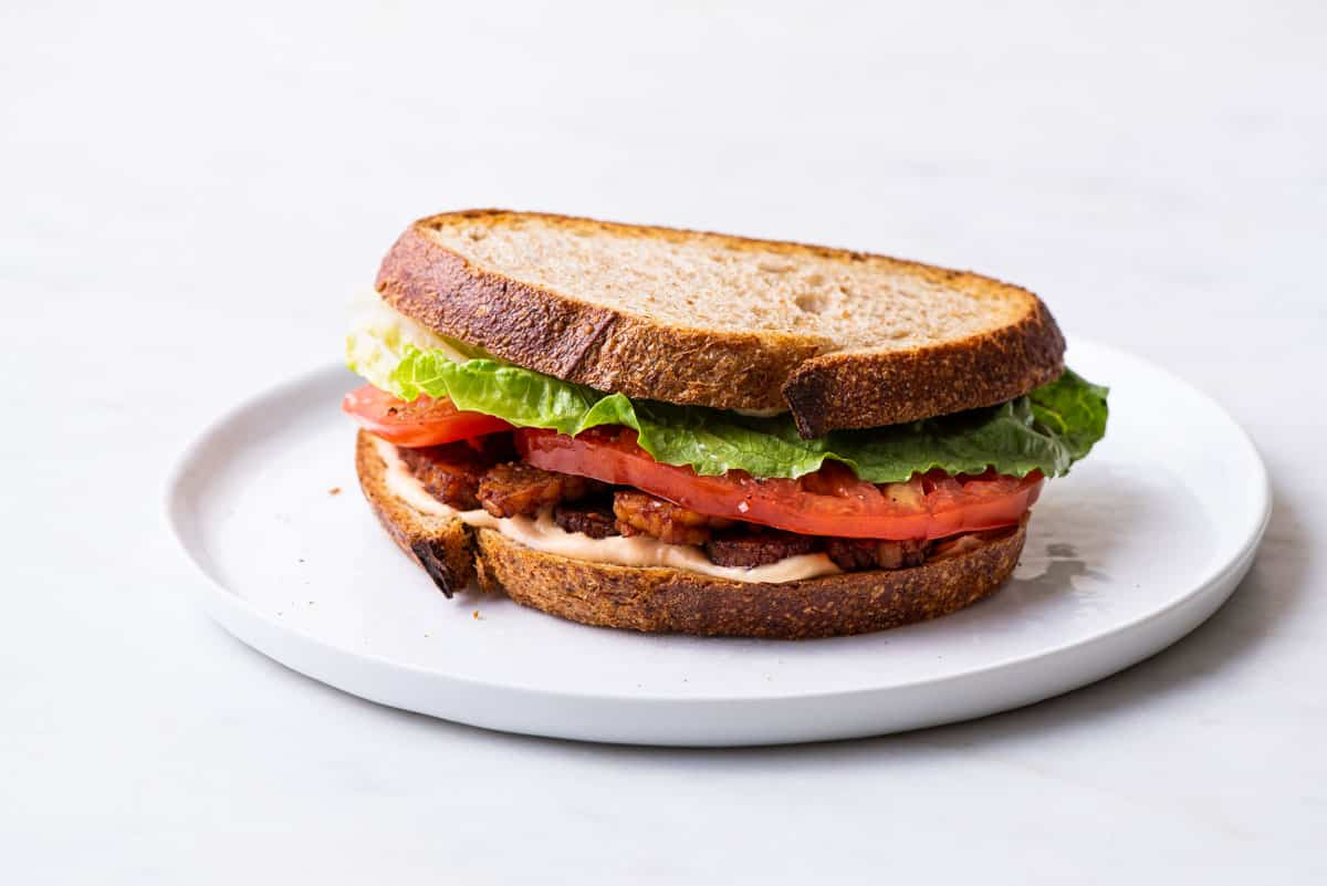 A vegan BLT sandwich with tempeh bacon on a white plate.
