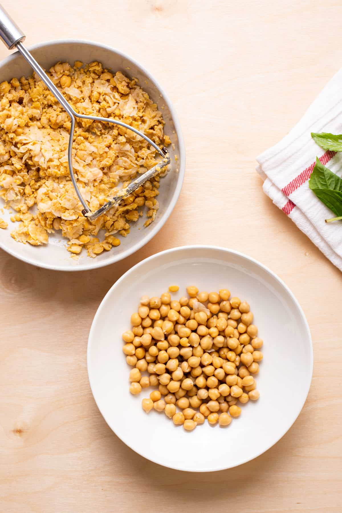 Whole and mashed chickpeas in two bowls.