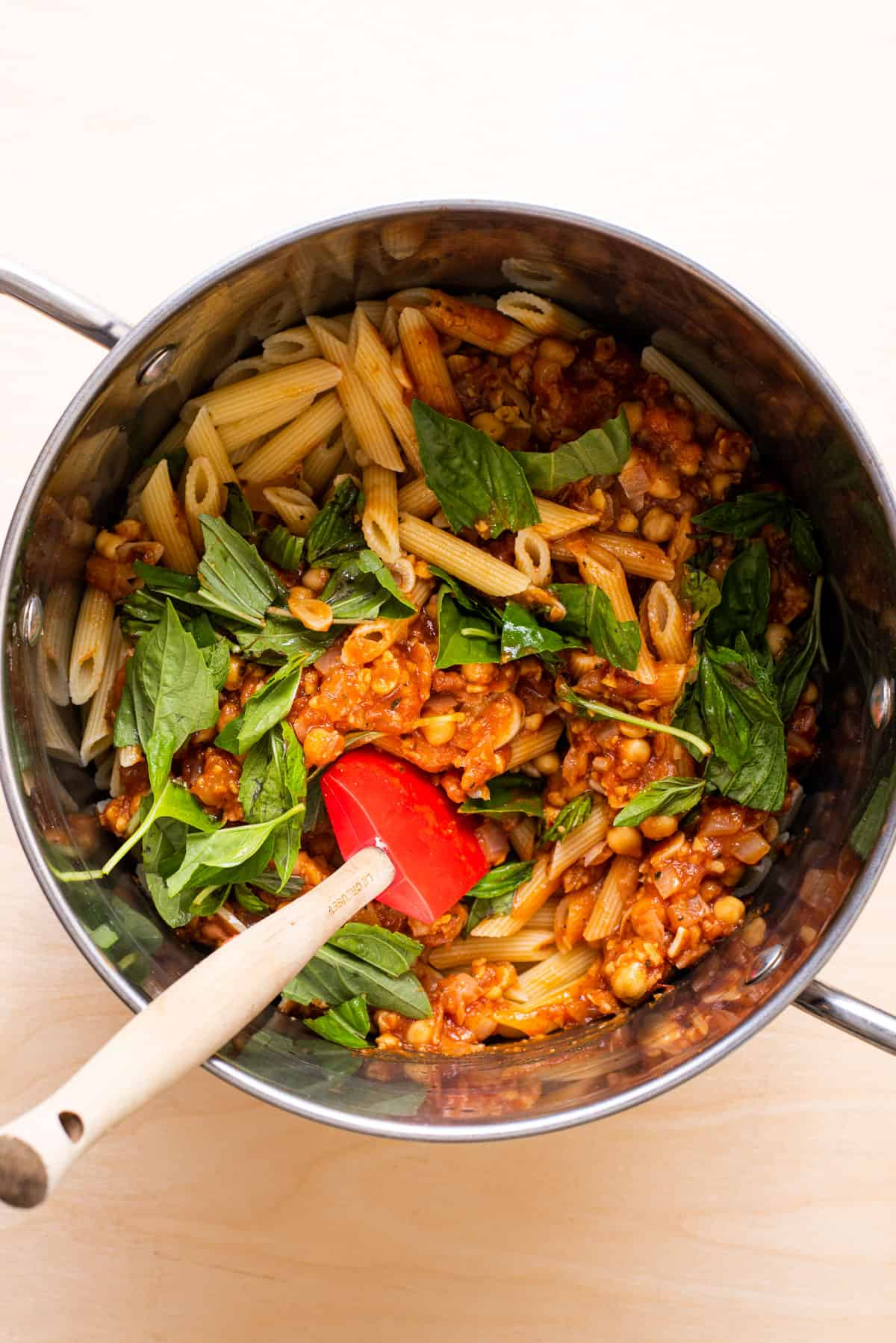 Cooked penne in a pot with chickpea-tomato sauce and torn basil.