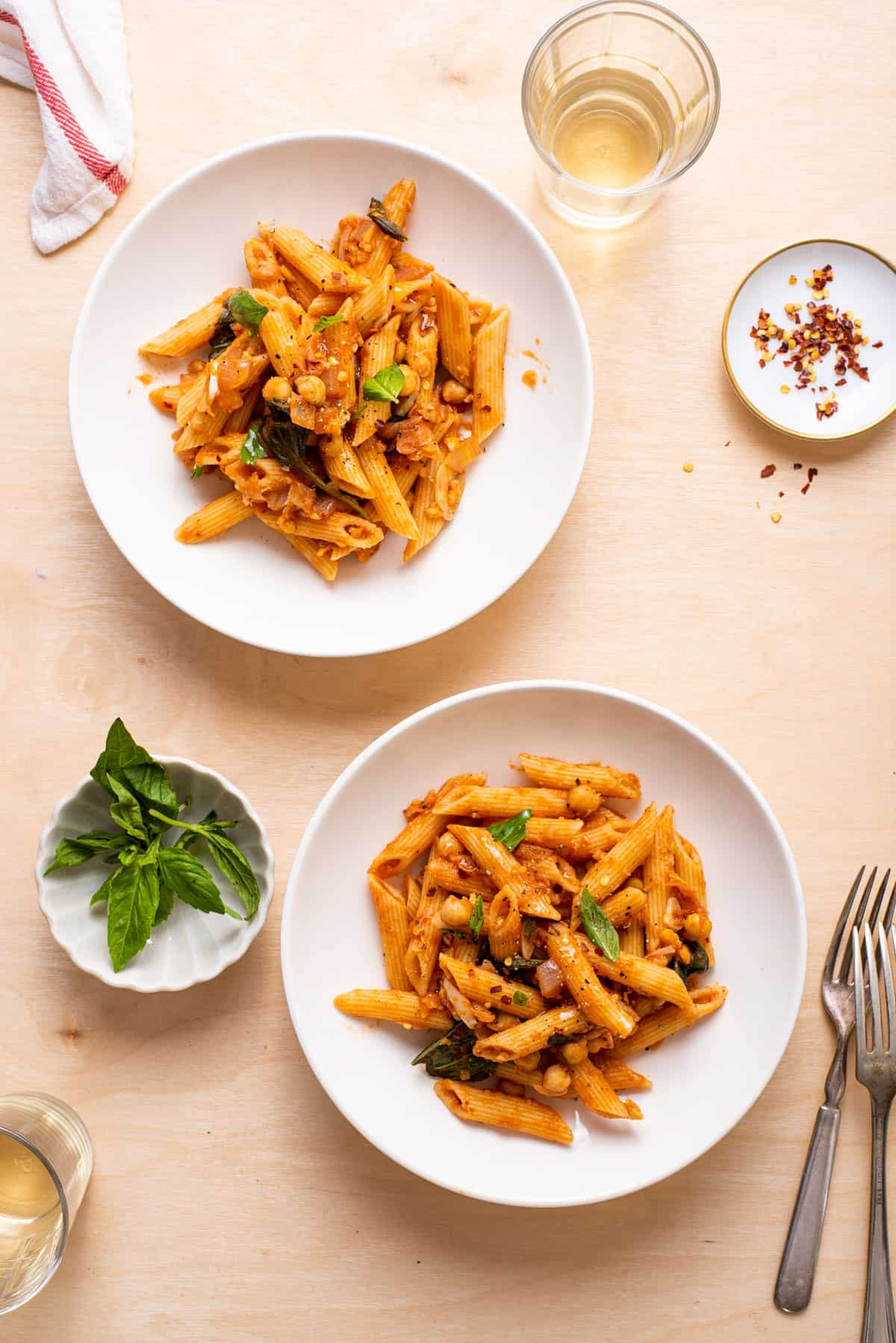 Two bowls of chickpea tomato pasta on a wooden table.