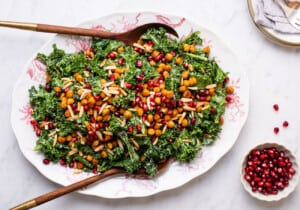 Massaged kale salad with tahini dressing and crispy chickpeas on an oval platter next to pomegranate seeds.