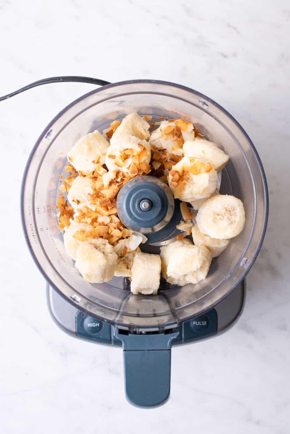 Frozen banana chunks in a food processor with toasted coconut flakes.