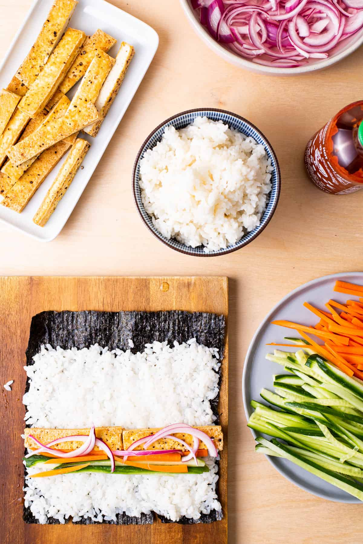 Making vegan sushi with tofu, raw veggies, and quick-pickled onions.