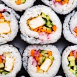 Close-up of veggie sushi with white rice, crispy tofu, carrots, and cucumbers.