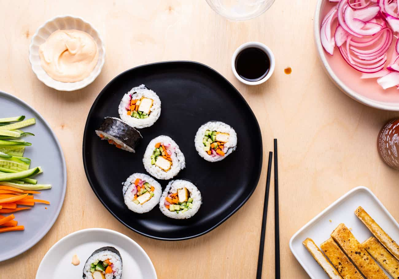 Vegan sushi rolls on a black plate next to spicy mayo and soy sauce on a wooden table.