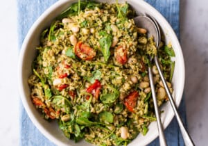 Summer rice salad with pesto and tomatoes in a beige bowl on a blue napkin.
