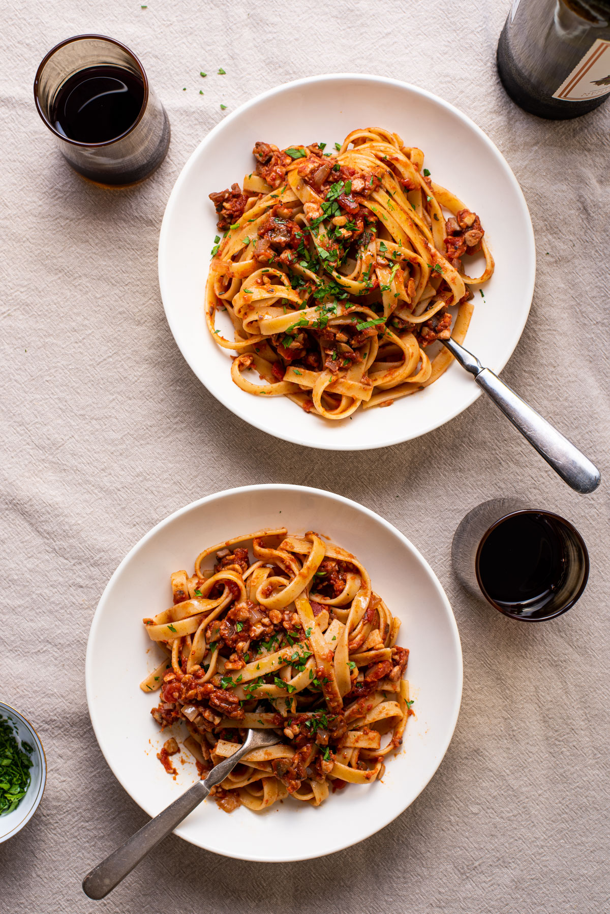 Fettuccine with tempeh bolognese in 2 white bowls on a beige tablecloth next to red wine.