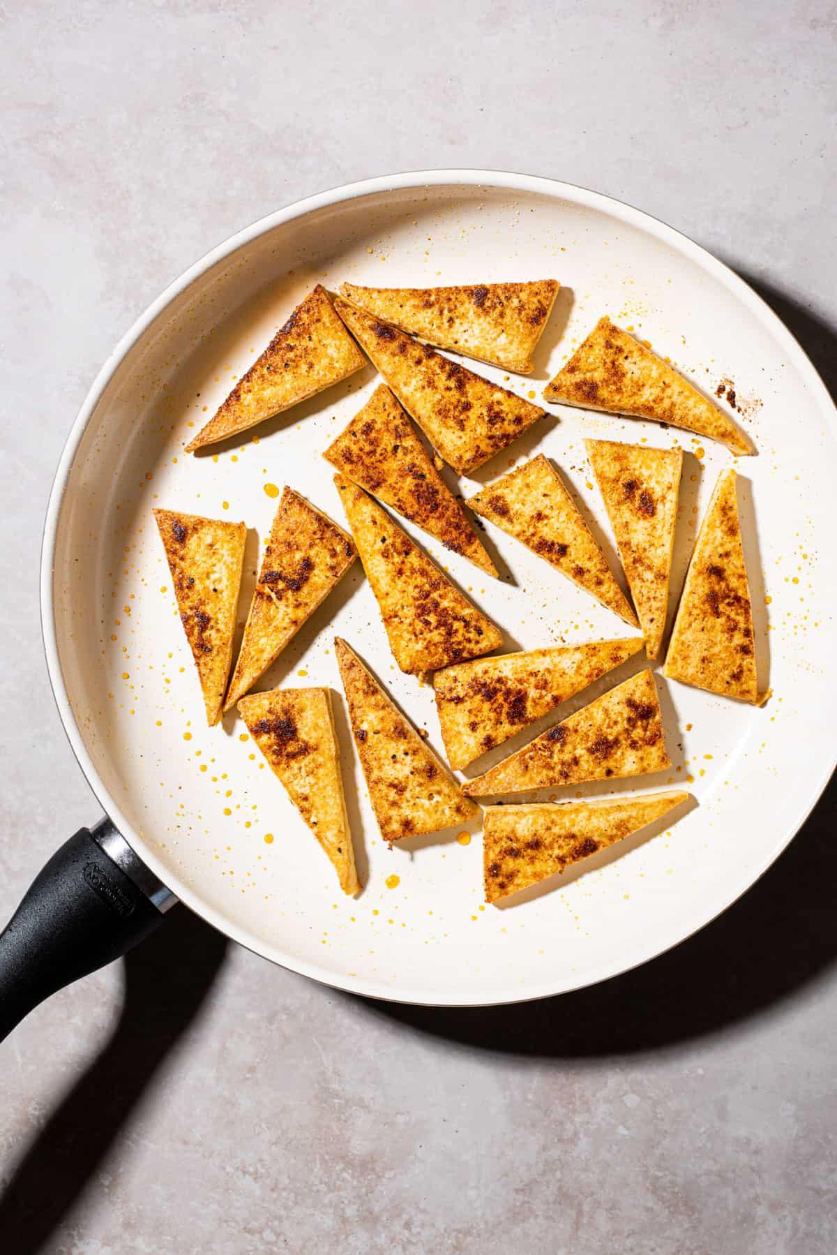 Seared tofu triangles in a non-stick skillet.