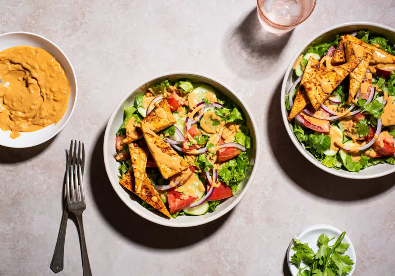 2 bowls of Thai salad with peanut dressing and seared tofu.