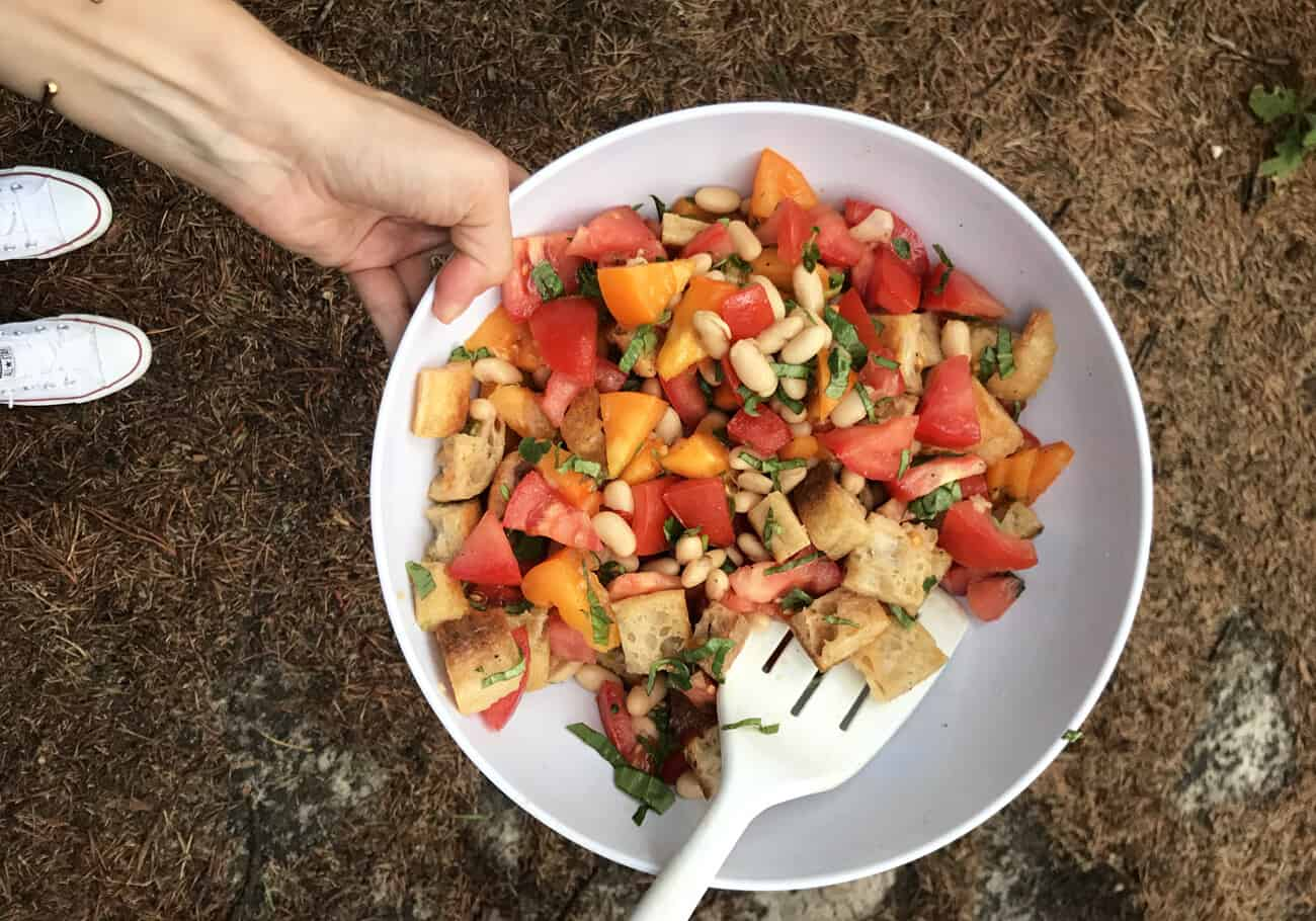 Woman's hand holding a bowl of panzanella while camping.