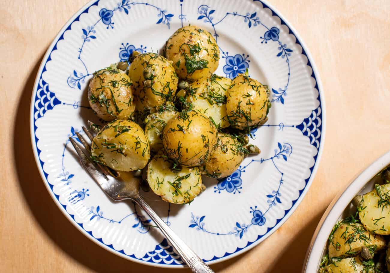 Herbed potato salad on a vintage plate on a wooden table.