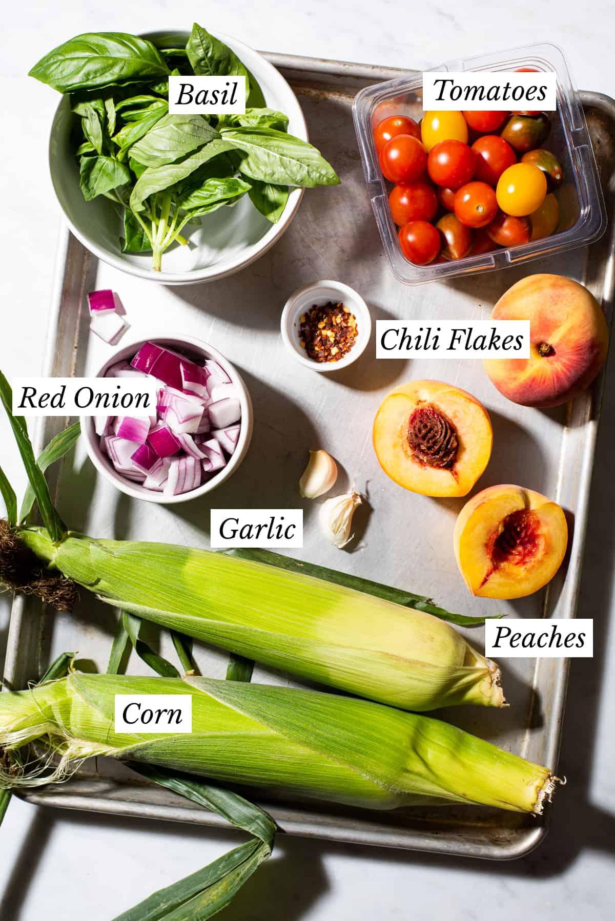 Ingredients gathered to make tomato peach salad on a metal baking sheet.