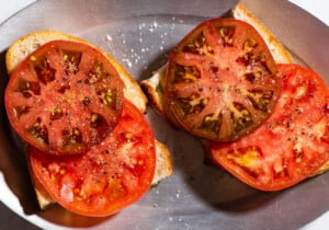 2 pieces of heirloom tomato toast on a sizzle plate.