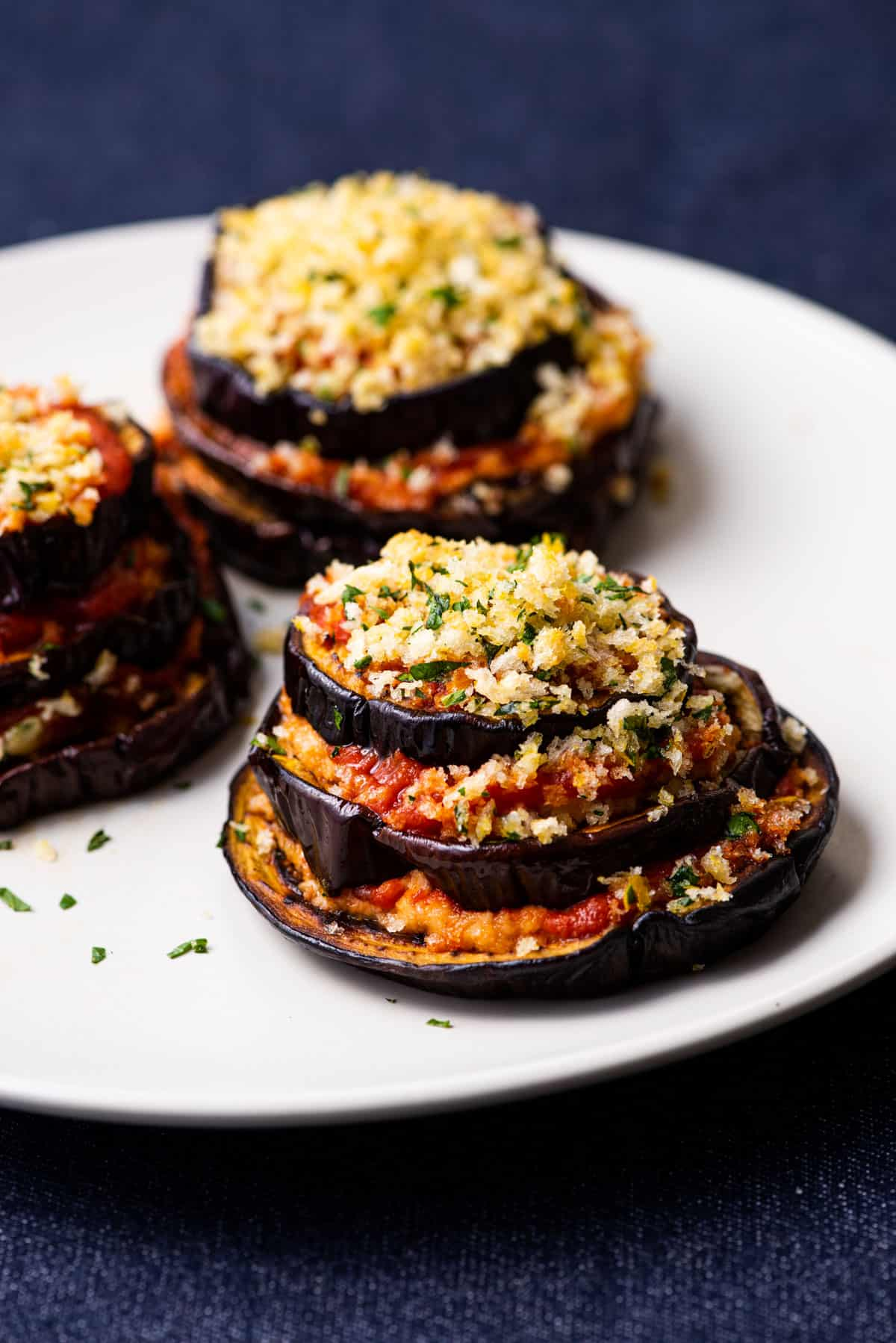 Vegan eggplant lasagna stacks with crunchy Panko topping, on a beige plate on a blue tablecloth.