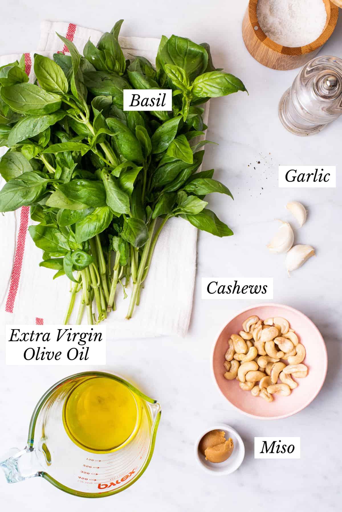 Ingredients gathered to make the best vegan pesto: basil, cashews, garlic, olive oil.