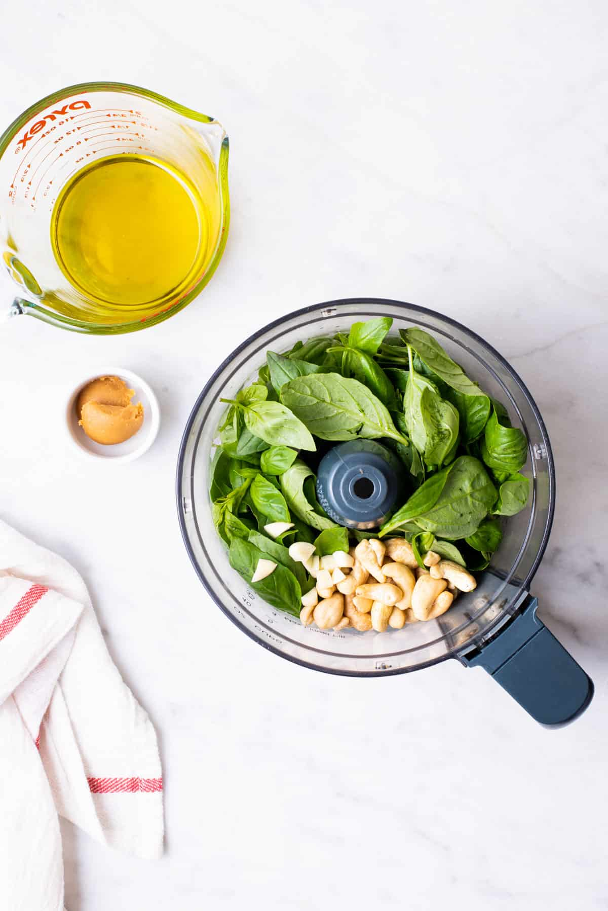 Basil, cashews, and garlic in a food processor next to a Pyrex measuring cup with olive oil.