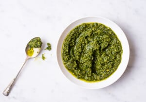 Homemade vegan pesto in a white bowl on a marble table.