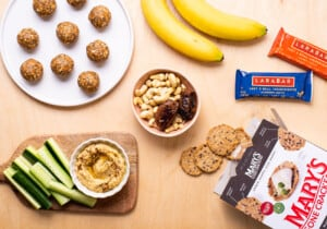 Healthy snacks on a wooden table, including energy balls, hummus, nuts, and bananas.