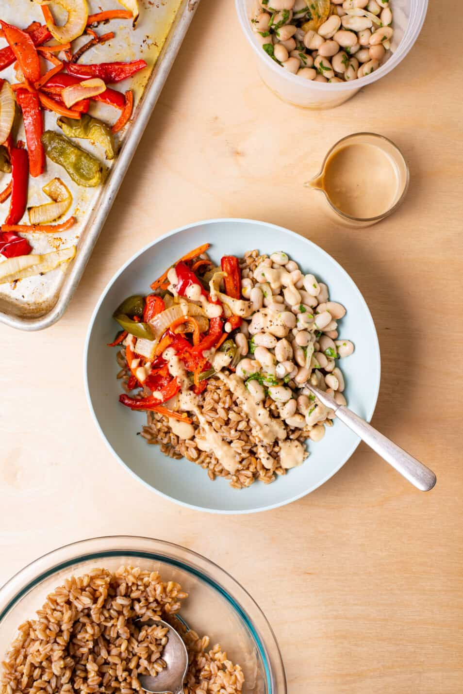 Farro bowl next to a tray of roasted vegetables, white bean salad, and tahini dressing.