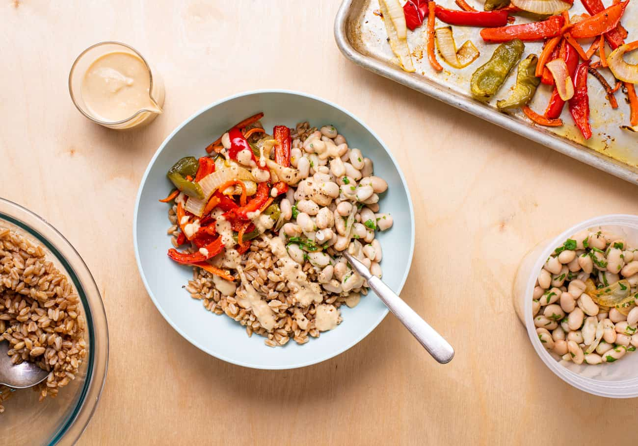 Farro bowl next to a tray of roasted vegetables, herby white beans, and lemon tahini dressing.