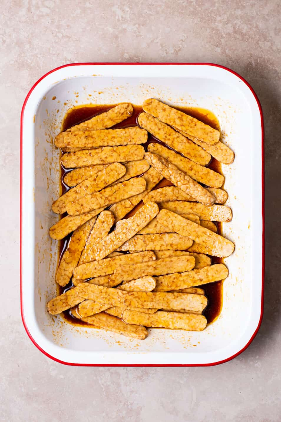 Tempeh strips marinating in an enamel dish.