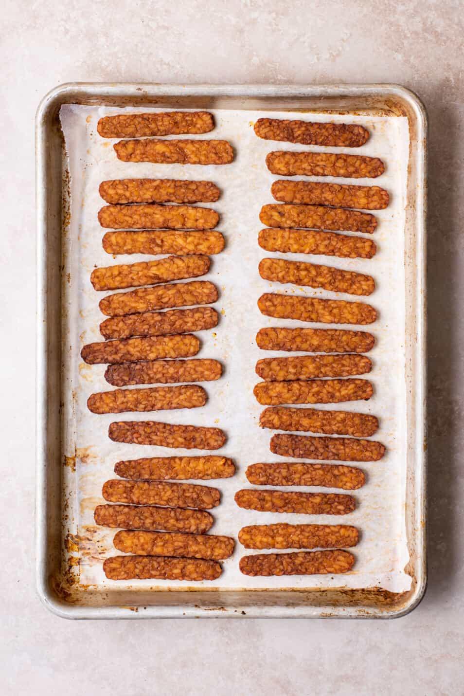 "Vegan tempeh ""bacon"" strips on a baking sheet."