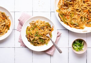 Bowl of stir fried noodles with vegetables next to sliced scallions.
