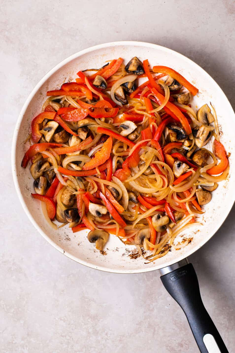 Sauteed peppers, onions, and mushrooms in a skillet.